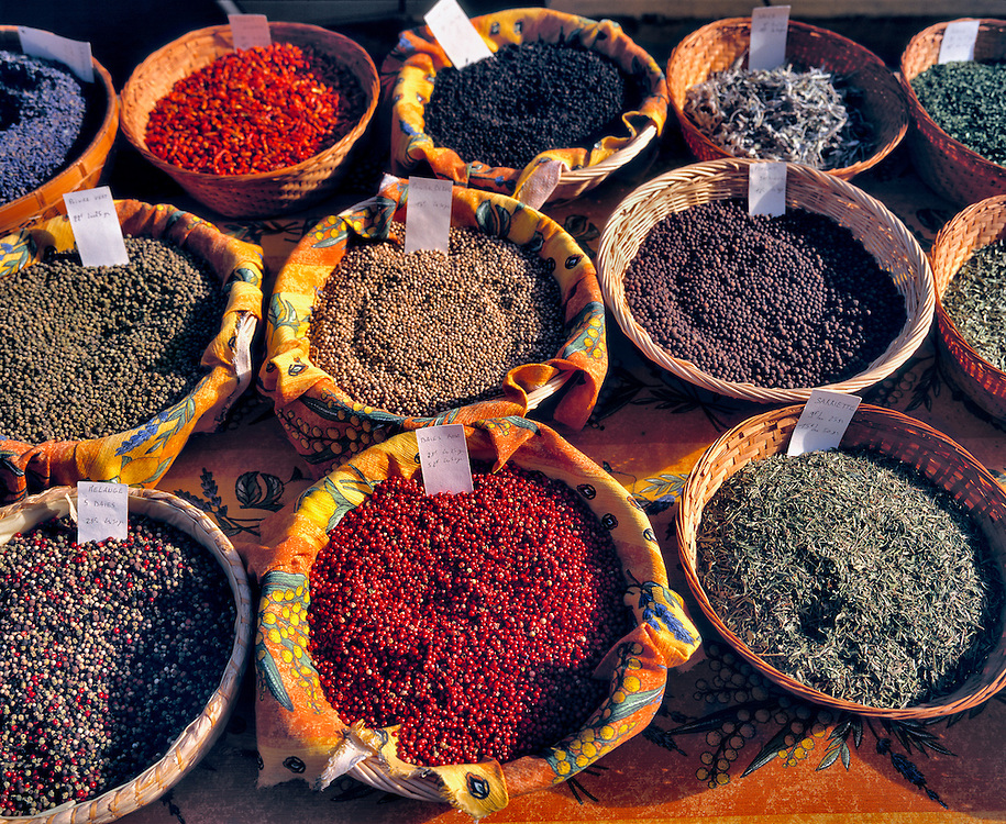 Baskets of colorful spices tempt shoppers at an outdoor market in Forcalquier, Provence, France.