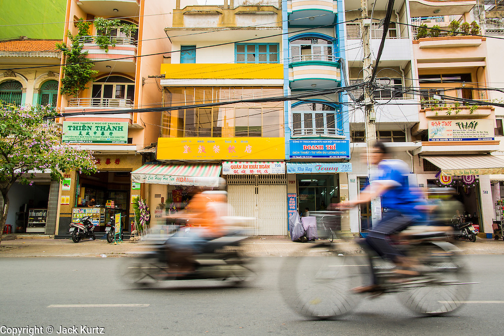 """12 APRIL 2012 - HO CHI MINH CITY, VIETNAM:  Traffic on a street in Cholon. Cholon is the Chinese-influenced section of Ho Chi Minh City (former Saigon). It is the largest """"Chinatown"""" in Vietnam. Cholon consists of the western half of District 5 as well as several adjoining neighborhoods in District 6. The Vietnamese name Cholon literally means """"big"""" (lon) """"market"""" (cho). Incorporated in 1879 as a city 11km from central Saigon. By the 1930s, it had expanded to the city limit of Saigon. On April 27, 1931, French colonial authorities merged the two cities to form Saigon-Cholon. In 1956, """"Cholon"""" was dropped from the name and the city became known as Saigon. During the Vietnam War (called the American War by the Vietnamese), soldiers and deserters from the United States Army maintained a thriving black market in Cholon, trading in various American and especially U.S Army-issue items.         PHOTO BY JACK KURTZ"""