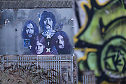 Street art mural of iconic local band Black Sabbath looking across disused ground, in the industrial area of Deritend, which lies less than half a mile from the city centre on 7th January 2021 in Birmingham, United Kingdom. Black Sabbath were an English rock band formed in Birmingham in 1968 by Tony Iommi, Bill Ward, Geezer Butler and Ozzy Osbourne. They are often cited as the pioneers of heavy metal music.
