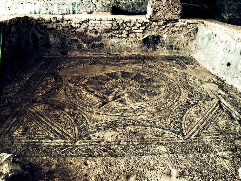 View of a room in the ancient Roman sanitarium at Almendinilla with monochrome floor mosaics with symmetrical curvelinear designs.