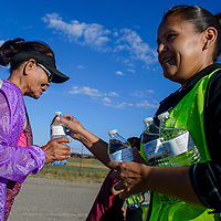 RaeNell Platero, left, passes a bottle of water toAlice Begay during a health walk in Pine Hill Thursday.