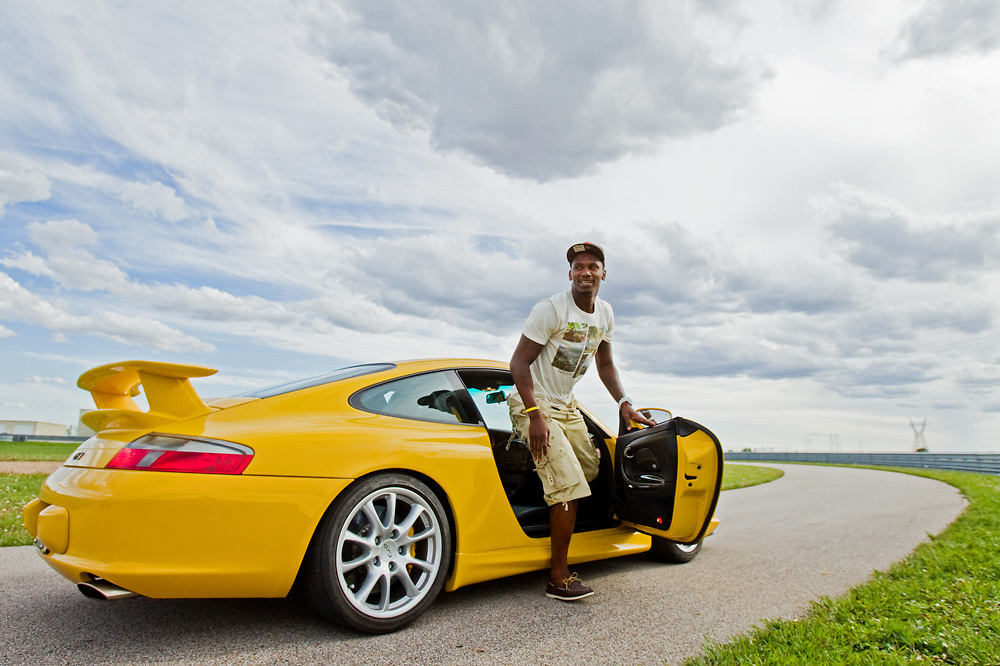 Nebraska Danger wide receiver Corey Surrency gets out of a 2004 Porsche 911 owned and driven by Robert Anderson of Hastings after a ride Friday at Motorsports Park in Hastings. Nebraska Danger owner Charlie Bosselman invited the team out for fun before going to dinner in Hastings. (Independent/Matt Dixon)
