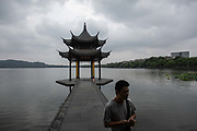 A man walks near a pavilion on the waterfront of West Lake in Hangzhou, China, on Monday, Sept. 5, 2016. The lake, a popular and crowded tourist destination, saw a rare quiet day as the government shut the area down for tourists and residents alike for the G20 meeting held in the city, returning the lake to its serenity of the old days.