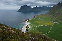 Female hiker descends Veggen mountain peak with Uttakleiv beach in backround, Vestvågøy, Lofoten Islands, Norway