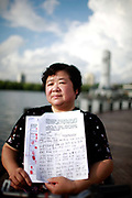 Lu Yafang, an investor who claimed that she lost her life saving of 100,000 RMB (roughly 15,500 USD) to investment schemes promoted by the local government, shows a signed petition and thumb prints of other victims in Shanghai, China on 04 August, 2011. With the banking interest rate artificially depressed by the Chinese government, the average Chinese citizen has little option to increase their wealth in the face of inflation, causing some of them to put their money in risky and often fraudulent schemes.