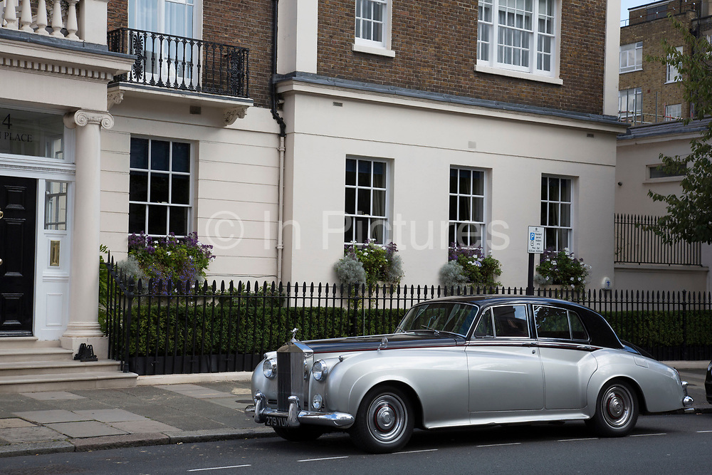 Vintage Rolls Royce Silver Cloud car parked in front of the classic architecture in Belgravia London, United Kingdom. Belgravia is a district in West London in the City of Westminster and the Royal Borough of Kensington and Chelsea. It is noted for its very expensive residential properties and is one of the wealthiest districts in the world. Much of it, known as the Grosvenor Estate, is still owned by a family property company, the Duke of Westminsters Grosvenor Group.