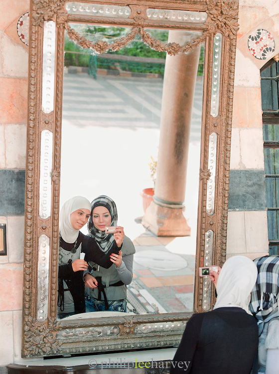 Young girls photograph themselves in the grounds of Azem Palace in the Old City in Damascus, Syria