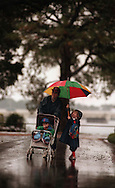 """Gabrielle Schreiber,5, holds the umbrella for her mother Nancy Schreiber and Elliot Schreiber,20 months, while walking several blocks down Gilliland Rd in Navy Point from the baby sitters. """"I let my husband us my car because his was giving him problems and I figured the rain would stop,"""" Nancy said."""