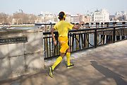 Man dressed in yellow shorts, socks, t-shirt and headphones power walking along the Southbank at Queens Walk. Going at a very fast pace, turning heads as he goes. The South Bank is a significant arts and entertainment district, and home to an endless list of activities for Londoners, visitors and tourists alike.