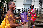 Man from UK Chocolate Nation threatens to throw chocolate over a woman selling shots of Morgans Spiced Rum at Notting Hill Carnival in West London. The Notting Hill Carnival is an annual event which since 1964 has taken place each August, over two days (the August bank holiday Monday and the day beforehand). It is led by members of the West Indian / Caribbrean community, particularly the Trinidadian and Tobagonian British population, many of whom have lived in the area since the 1950s. The carnival has attracted up to 2 million people in the past, making it the second largest street festival in the world. The celebration centres around a parade of floats, dancers and sound systems.