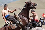 Horseback wrestling competition (Er-Enish) at a traditional Kyrgyz horse games festival. Bosogo jailoo, Naryn province, Kyrgyzstan.