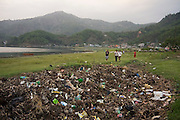 Piles of partially burned and buried garbage waste away on the shore of Lake Phewa Tal in Pokhara, Nepal.