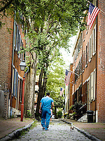 A man walks his dog down a cobble stone street in the historic Society Hill section of Philadelphia.