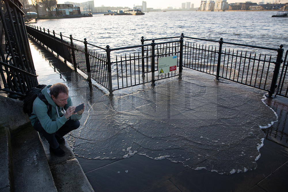 © Licensed to London News Pictures. 22/02/2019. London, UK. A man takes a photo as an extreme high tide causes the River Thames to flood onto the Thames Path. The weather is also unseasonably warm in the capital, with temperatures set to reach 16 degrees Celsius this weekend. Photo credit : Tom Nicholson/LNP