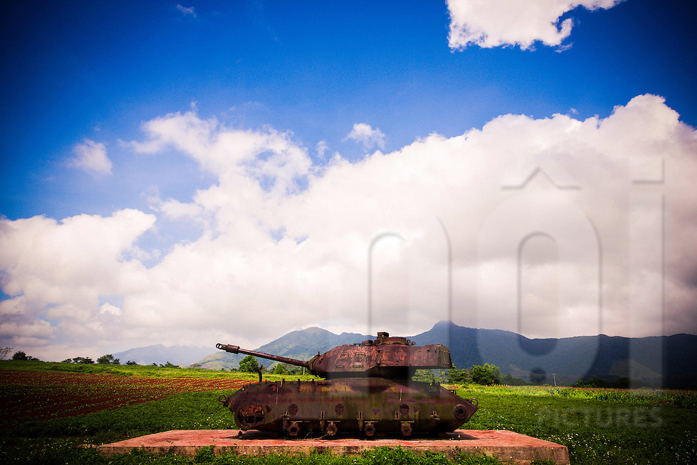 Old rusty military tank on display in a lush green field at Khe Sanh Combat Base, DMZ, Quang Tri Province, Vietnam, Southeast Asia