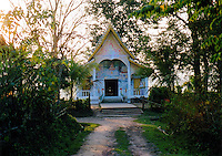 """Laos, Luang Nam Tha, 2003. Though this tiny Buddhist temple, or """"wat,"""" is far from town, it is home to two young brothers, who maintain it with care."""