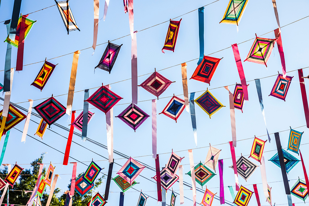 """Ojo de Dios or """"God's Eye"""", a local symbol and craft of the indigenous Huichol culture hang from wires above the streets of Sayulita, Nayarit, Mexico."""