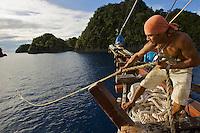 Crewman on the Shakti pulls on a mooring line..Misool Island vicinity.  Near smaller island of Fiabacet.