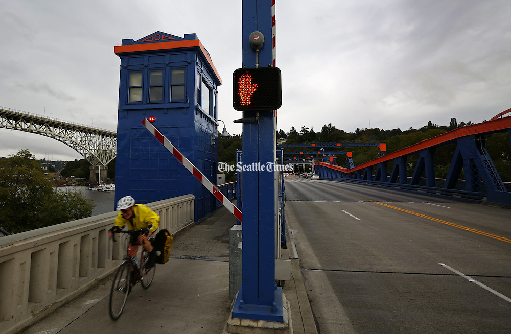 Seattle's bridges are more than just connectors, we interact with them, like this cyclist peddling fast northbound over the Fremont Bridge.<br /> <br /> Ken Lambert / The Seattle Times