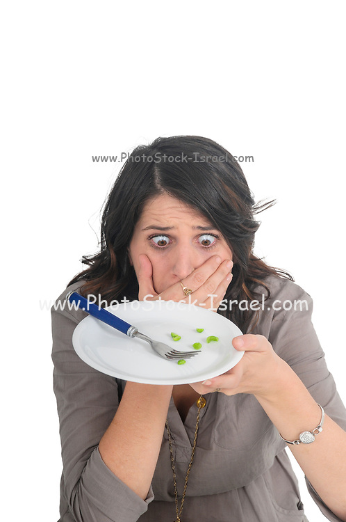 exaggerated approach to Eating Disorders. The sickness of the 21st century Anorexia and eating disorder concept young woman eats a single pea on a large white plate studio shot on white background