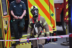 © Licensed to London News Pictures. 01/04/2020. London, UK. LFB (London Fire Brigade) using full face respirators normally reserved for firefighting at an incident involving all emergency services a suspected COVID-19 case is isolated and removed from home. Uxbridge Road in Shepherd's Bush was closed for an hour as ambulance, fire brigade and police attended, extracting the patient by crane from a three story apartment building in West London. PPE (personal protective equipment) was in evidence, with the fire brigade. Ambulance workers decontaminated the scene and reusable equipment before moving on.  Photo credit: Guilhem Baker/LNP