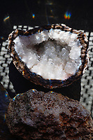 """Geodes (derived from the Greek word """"γεώδης"""" meaning """"Earth-like"""") are geological secondary formations within sedimentary and volcanic rocks. Geodes are hollow, vaguely circular rocks, in which masses of mineral matter (which may include crystals) are secluded. The crystals are formed by the filling of vesicles in volcanic and sub-volcanic rocks by minerals deposited from hydrothermal fluids; or by the dissolution of syn-genetic concretions and partial filling by the same, or other, minerals precipitated from water, groundwater or hydrothermal fluids.  -Wikipedia"""