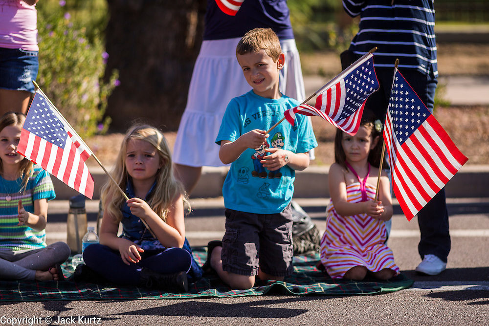 """11 NOVEMBER 2013 - PHOENIX, AZ: Spectators cheer passing veterans at the Phoenix Veterans Day Parade. The Phoenix Veterans Day Parade is one of the largest in the United States. Thousands of people line the 3.5 mile parade route and more than 85 units participate in the parade. The theme of this year's parade is """"saluting America's veterans.""""     PHOTO BY JACK KURTZ"""