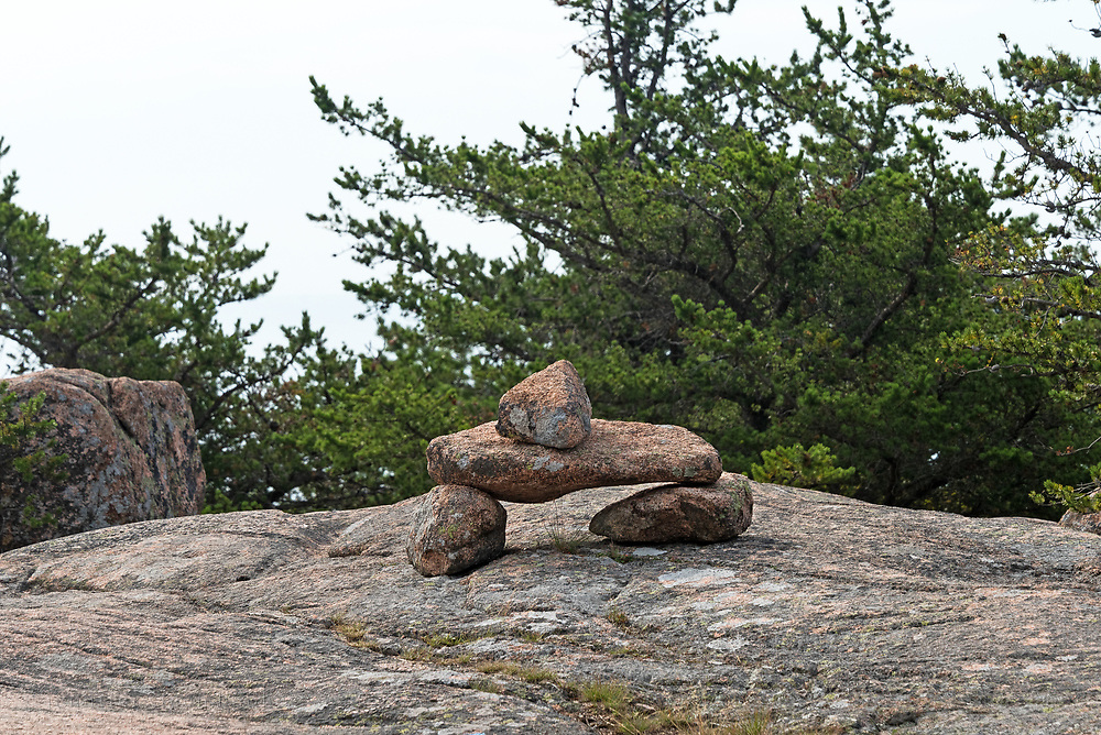 Bates cairns and Jack Pine (Pinus banksiana) mark a bare granite section of the South Ridge trail of Cadillac Mountain, Acadia National Park, Maine, USA