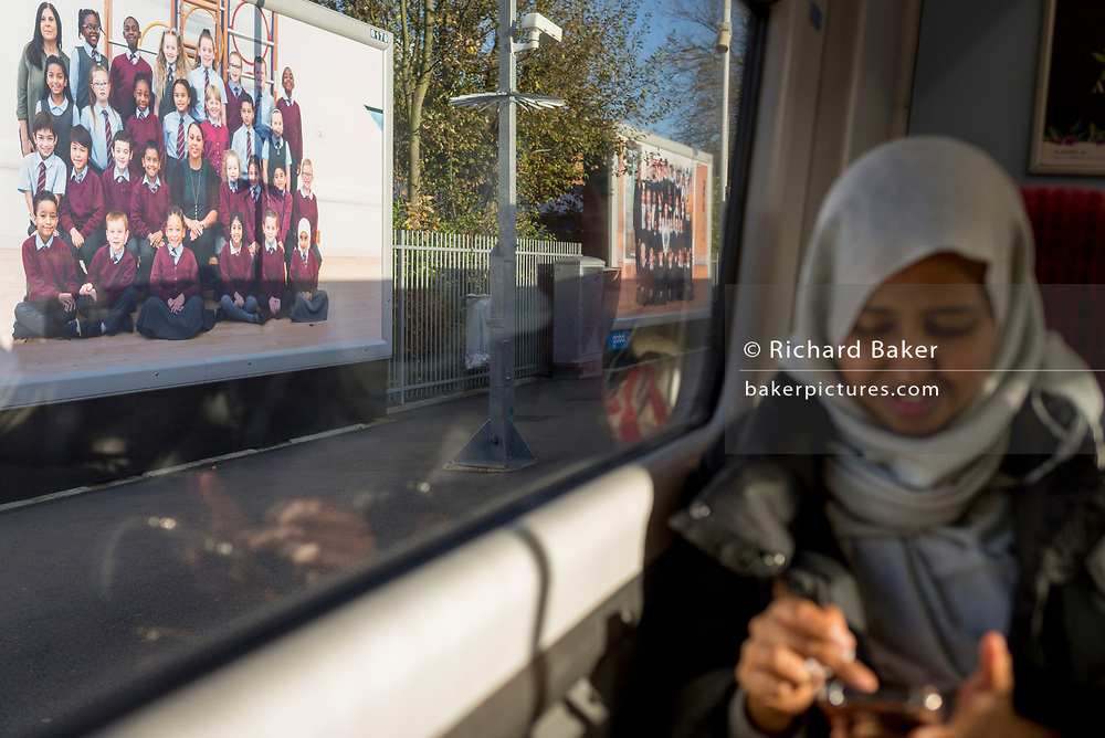 "A train passenger uses her phone as billboard ad portraits by artist Steve McQueen's school children portraits artwork, on 7th November 2019, in Kingston, London, England. Portraits of schoolchildren by the artist Steve McQueen have been unveiled on billboards across London. The Oscar-winning filmmaker, photographed thousands of London's Year Three pupils, in traditional-style class snaps with rows of smiling children alongside their teachers, for a ""visual portrait of citizenship"". The portraits are on display at 613 locations on roadsides, railways and underground stations. Turner Prize-winner McQueen invited all of London's Year Three school pupils to take part but ended up with 76,000 children – around two thirds of London's seven to eight-year-olds. The outdoor work is a collaboration with Artangel, known for producing unusual art in unexpected places."