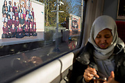 """A train passenger uses her phone as billboard ad portraits by artist Steve McQueen's school children portraits artwork, on 7th November 2019, in Kingston, London, England. Portraits of schoolchildren by the artist Steve McQueen have been unveiled on billboards across London. The Oscar-winning filmmaker, photographed thousands of London's Year Three pupils, in traditional-style class snaps with rows of smiling children alongside their teachers, for a """"visual portrait of citizenship"""". The portraits are on display at 613 locations on roadsides, railways and underground stations. Turner Prize-winner McQueen invited all of London's Year Three school pupils to take part but ended up with 76,000 children – around two thirds of London's seven to eight-year-olds. The outdoor work is a collaboration with Artangel, known for producing unusual art in unexpected places."""