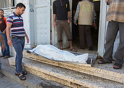 © Licensed to London News Pictures. 17/07/2014. Gaza.   <br /> *WARNING - IMAGE CONTAINS CONTENT OF A GRAPHIC NATURE*<br /> <br /> The family of Mohammed Rahman take his body away to be buried from the Gaza city morgue.  Mohammed was killed in an Israeli strike in the Sheikh Ajnein district of Gaza on the 16 Jul 14.  Photo credit : Alison Baskerville/LNP