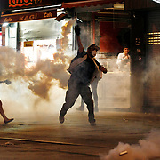 A Turkish protester throws back a gas canister used to disperse protesters by police during an anti-government protest at Taksim Square in Istanbul, Turkey, 06 July 2013. Photo by AYKUT AKICI/TURKPIX