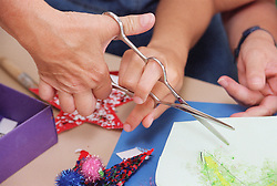 Close up of carer and patient's hands using dual control training scissors,