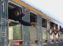 © London News Pictures. 06/09/2015. A migrant gestures  from a train travelling from Budapest to Vienna at  the train station in Győr close to the border of Hungary and Austria, September 6 2015. Hundreds of migrants have resumed their journey through Austria to Germany after Hungary's decision on Friday to let them through. Picture by Paul Hackett/LNP