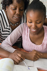 Mother helping daughter to study for school exams,