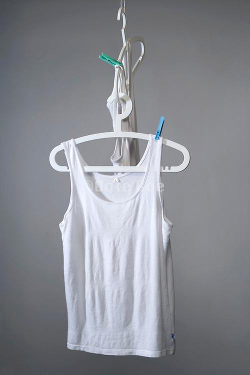 white t-shirts hanging on clothing hanger