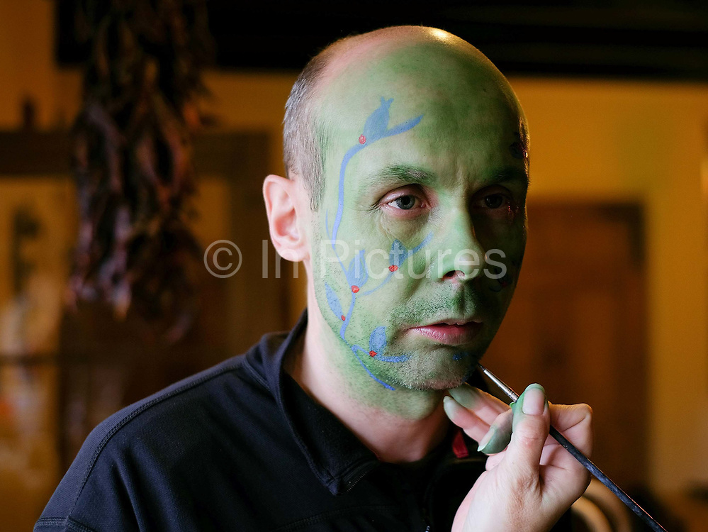 Making up the green man for an orchard-visiting wassail in Kilham village, Yorkshire Wolds, UK on 21st January 2017. Wassail is a traditional Pagan winter celebration in cider-producing regions of England, reciting incantations and singing to the trees to promote a good harvest for the coming year. Pieces of toast soaked in cider are hung in the branches to attract robins to the tree as these are said to be the good spirits of the orchard. To ward off evil spirits, villagers scare them away by banging pots and pans and making as much noise as possible