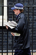 © Licensed to London News Pictures. 21/05/2013. Westminster, UK. A police officer delivers newspapers to number ten. Ministers arrive for a Cabinet meeting at Downing Street today 21 May 2013. Photo credit : Stephen Simpson/LNP