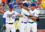 Kansas City Royals pitcher Danny Duffy, center, is held back from going after first base umpire Adam Hamari, (not pictured) by pitching coach Cal Eldred, right, and second baseman Whit Merrifield, left, in the sixth inning of a baseball game against the St. Louis Cardinals at Kauffman Stadium in Kansas City, Mo., Saturday, Aug. 11, 2018. Duffy was ejected from the game for arguing with Hamari about a checked swing call. (AP Photo/Colin E. Braley)