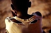 """An orphan boy of Burundi's ethnic conflict with a torn shirt. He lives in Shalom House that was founded by Marguerite Barankitse (known as the 'Angel of Burundi') in 1994. During the genocide, Barankitse, at great personal risk, managed to save 25 orphans, Hutu, Tutsi and Twa and built a home for them. Currently, she has helped more than 10,000 orphans and separated children who can grow up in an """"extended adopted family"""" in security, education and love. Burundi now has many 'child headed households'"""