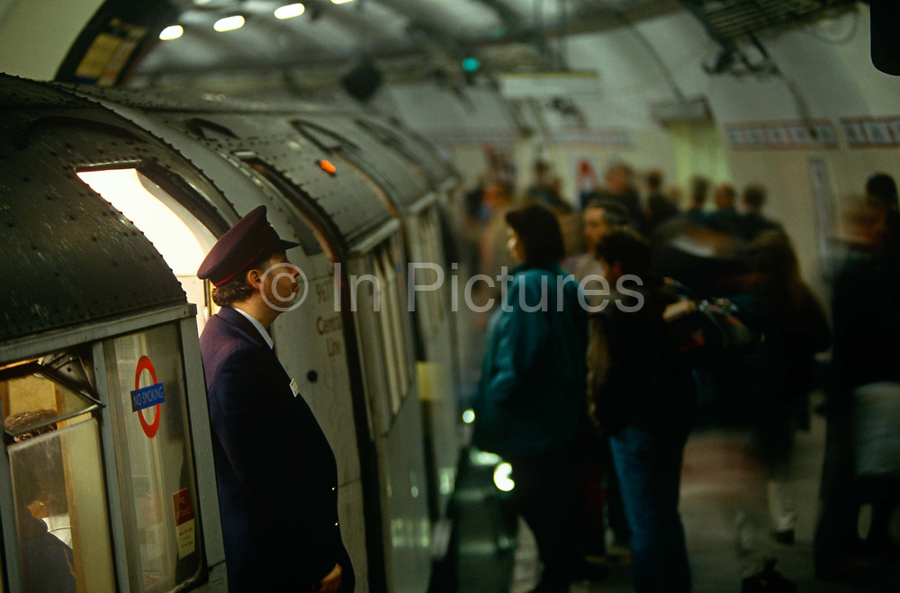 """During the morning rush-hour at Bank underground station in the heart of London's financial district, the grim face of 90s tube travel is seen here in a wide landscape of rounded tunnel and the curve of the station platform. A train guard watches for a green signal as Londoners are sandwiched inside the nearest carriage. Waiting for the doors to close and the hot air to seal them inside the small space, men and women press against each other in a claustrophobic journey along the Central Line. The Central line is a London Underground line, coloured red on the tube map. It is a deep-level """"tube"""" line, running east-west across London, and, at 76 km (47 mi). Incorporated in 1891 it is today the longest Underground line and also the busiest with around 260 million passengers a year."""