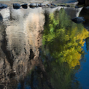 A rock formation and a tree with autumn color reflect off of the shallow pool of water along the Rogue River near Prospect, Oregon in the Cascade Mountains.