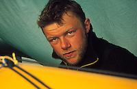Reperasjon av hull i kajakk etter at den har blitt angrepet av hvalross, repairing a whole in a kayak after being attaced by a whaleross, portrett av alvorlig mann, portrait of a sireous man's face