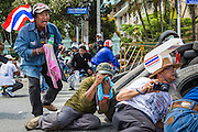 18 FEBRUARY 2014 - BANGKOK, THAILAND: Anti-government protestors in Bangkok look for police snipers while they take cover behind a tire barricade when police returned fire after somebody in the protestors fired towards police positions. Anti-government protestors aligned with Suthep Thaugsuban and the People's Democratic Reform Committee (PDRC) clashed with police Tuesday. Protestors opened fire on police with at rifles and handguns. Police returned fire with live ammunition and rubber bullets. The Bangkok Metropolitan Administration's Erawan Emergency Medical Centre reported that three civilians and a policeman were killed and 64 others were injured in the clashes between police and protesters.    PHOTO BY JACK KURTZ