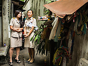 15 AUGUST 2016 - BANGKOK, THAILAND: Bangkok city officials walk through the Pom Mahakan slum in Bangkok after putting up eviction orders. Final eviction notices were posted today and residents of the slum have been told they must leave the fort by September 3, 2016. The Pom Mahakan community is known for fireworks, fighting cocks and bird cages. Mahakan Fort was built in 1783 during the reign of Siamese King Rama I. It was one of 14 fortresses designed to protect Bangkok from foreign invaders. Only two of the forts are still standing, the others have been torn down. A community developed in the fort when people started building houses and moving into it during the reign of King Rama V (1868-1910). The land was expropriated by Bangkok city government in 1992, but the people living in the fort refused to move. In 2004 courts ruled against the residents and said the city could take the land.      PHOTO BY JACK KURTZ