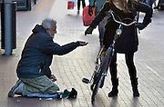 Nederland, Nijmegen, 19-1-2013Een bedelaar zit op zijn knieen en houdt zijn hand omhoog waar voorbijgangers geld in kan stoppen. Een jonge vrouw geeft hem wat muntgeld.De man komt uit Oost-Europa. Foto: Flip Franssen/Hollandse Hoogte