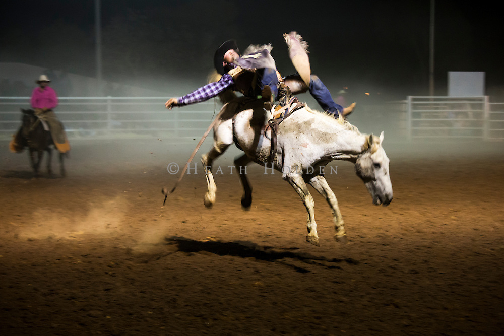 A cowboy riding a bareback bronco almost makes a full circle of the arena at the Tennant Creek rodeo.