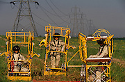 Standing in their cradles are three members of a National Grid Live-line electricity cable crew, protected in a conductive cage beneath the electricy cables that they maintaining. We see the sagging cables stretching to distant electricity pylons and the three human figures standing like astonauts in their protective cradles. Huge structure of girders and relays are behind them and they wear safety clothing allowing them to work comfortably inside the electrical field at close range with gloved hands. National Grid Electricity Transmission plc owns and operates the National Grid high-voltage electricity transmission network in England and Wales.National Grid plc is a United Kingdom based utilities company which also operates in other countries, principally in the United States.