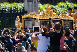 Crowds vye for a picture as the Queen leaves Parliament in her carriage after the opening of the Tory majority-led Parliament.
