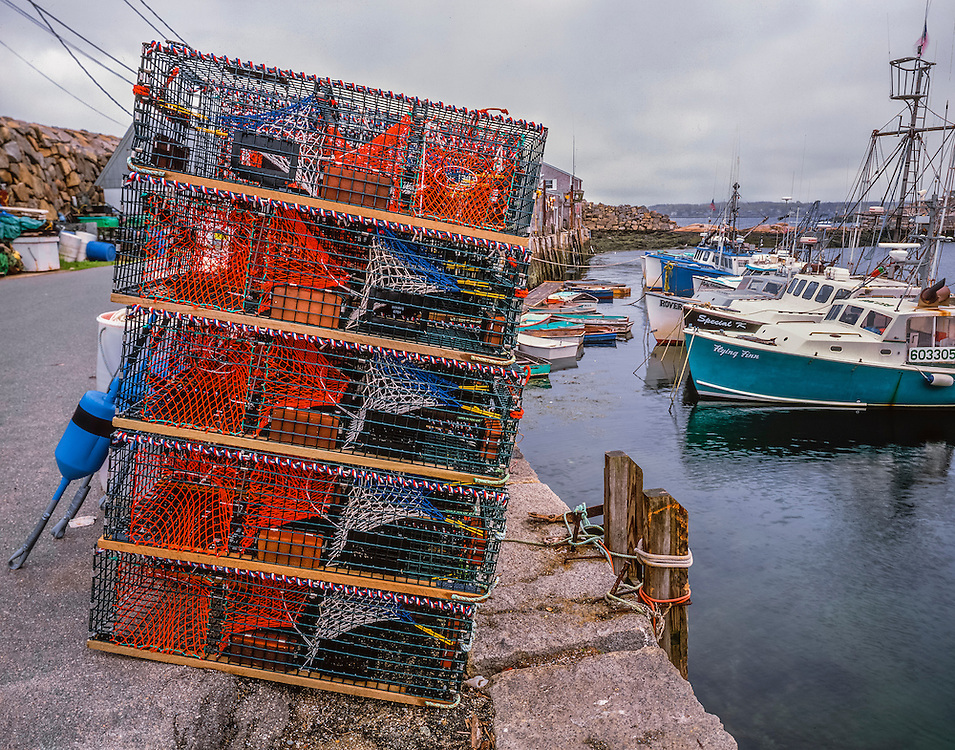 Lobster traps stacked & fishing boats in Pigeon Cove, Rockport, MA